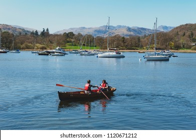 South Lakeland, UK - April 2018: Tourists rowing boat on scenic Windermere in Lake District National Park, North West England, UK