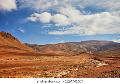In South Morocco, near the village of El Kelaa M'Gouna, a dirt track winds up to the snowy mountains of the atlas