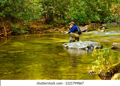 South Mountain State Park, North Carolina - 10/28/2018: A man fly fishing on Jacob Fork Creek as it winds through South Mountain State Park, North Carolina