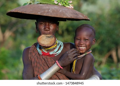SOUTH OMO - ETHIOPIA - OCTOBER 15, 2017: Unidentified Suri woman with lipplate and child in Lower Omo Valley
