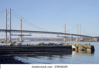 The South Queensferry side of the Forth Road Bridge, with two partially-completed towers of the new Queensferry Crossing Bridge in the background. South Queensferry Harbour is in the foreground.