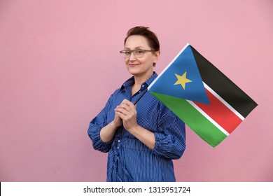 South Sudan flag. Woman holding South Sudan flag. Nice portrait of middle aged lady 40 50 years old holding a large flag over pink wall background on the street outdoors.