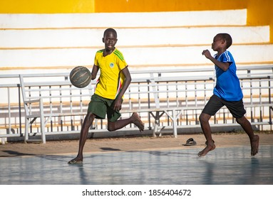 South Sudanese teenagers play on the side of the stadium while former players of South Sudan's national basketball team play with friends at Nimra Talata Stadium Juba South Sudan on 2017-07-25