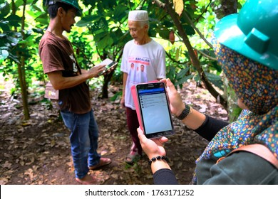 South Sulawesi, Indonesia - February, 2020: Technology helping farmers in agricultural sector to improve the productivity. Young farmer collecting data and information using tablets.