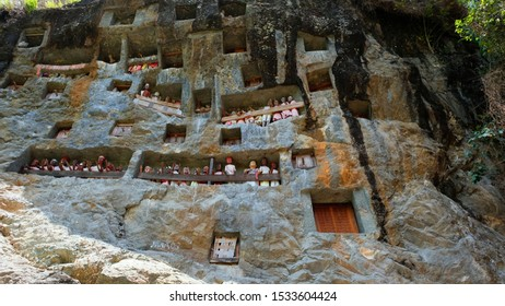 SOUTH SULAWESI, Indonesia - OCT. 17, 2019 : The burial site with coffins placed in caves carved into the rock, guarded by balconies of dressed wooden statues, images of the dead persons in Lemo.