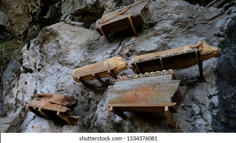 SOUTH SULAWESI, Indonesia - OCT. 18, 2019 : Hanging coffins, graves. Old coffin with skulls and bones nearby on a rock. Traditional burials site, cemetery Kete Kesu in Tana Toraja, South Sulawesi.