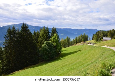 South Tirol in Italy, hiking area around the municipality of Percha near the town of Bruneck, mountain range on horizon, meadow and forest, a hiking trail on the right, sunny day in autumn, cloudy sky