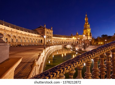 South tower, pool and bridge in the renaissance revival 'Plaza de Espana' in Seville illuminated at dusk