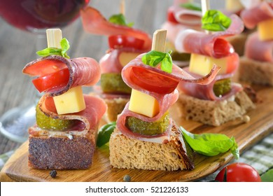 South Tyrolean appetizers: Buttered fresh farmhouse bread with smoked bacon, hearty mountain cheese, pickles and tomatoes, basil leaves on the top