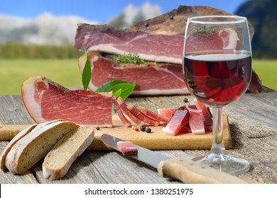 South Tyrolean bacon snack with local rye bread and a glass of red wine in front of alpine pastures and mountains of the alps