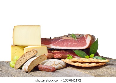 South Tyrolean specialties like bacon, sausages and cheese lying on a rustic table in front of a white background