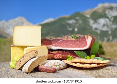 South Tyrolean specialties like bacon, sausages and cheese lying on a rustic table in front of mountains of the alps
