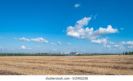 South Ukrainian Nuclear Power Plant and Wheat field against the blue sky with white clouds