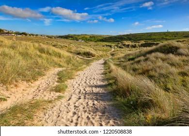 The South West Coast Path passes through sand dunes near Holywell Bay, Cornwall, UK.