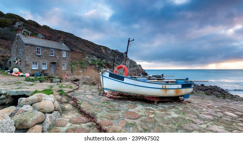 The South West Coast Path as it passes through fishing boats and cottages at Penberth Cove near Penzance in Cornwall