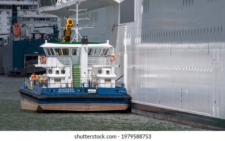 Southampton, England, UK. 2021. Seagreen a port based supply vessel collecting recycleble materials, alongside a cruise ship. In the Port of Southampton.