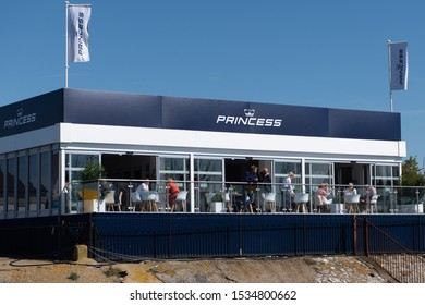 Southampton, Hampshire/UK - September 13 2019: Princess Yachts sales office at Southampton Boat Show. People on the terrace stand under a glass frontage, with with blue sign at the top.