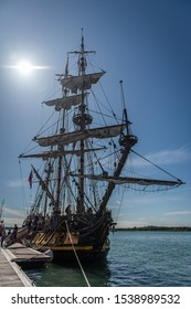 Southampton, Hampshire/UK - September 13 2019: Stylised shot of an old wooden square rigger against a blue sky with the sun in shot. Almost silhouette. Sun is blown out.