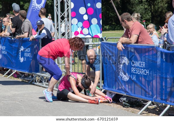 Southampton, Uk - 2 July 2017: Athlete, suffering from heat exhaustion, is help by bystanders at the finish line of Race for Life. This annual race is run by women to raise money for Cancer Research.