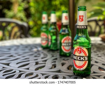 Southampton, UK - 2nd June 2020: Becks beer bottles on a garden table during an early summer hot spell of sunny weather.