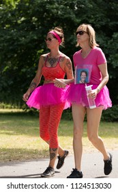 SOUTHAMPTON, UK - July 1 2018: Race for Life, women run and walk to raise money for Cancer Research charity, in Southampton UK. Women dressed up in a tutu walking under trees.