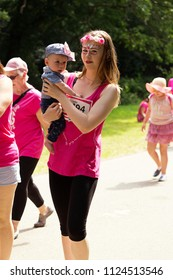 SOUTHAMPTON, UK - July 1 2018: Race for Life, women run and walk to raise money for Cancer Research charity, in Southampton UK. Mother with face paints holding her son whilst walking the race for life