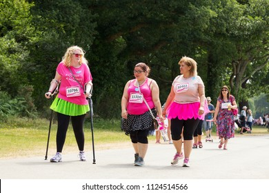 SOUTHAMPTON, UK - July 1 2018: Race for Life, women run and walk to raise money for Cancer Research charity, in Southampton UK. Women dressed up walking using crutches under trees.