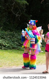 SOUTHAMPTON, UK - July 1 2018: Race for Life, women run and walk to raise money for Cancer Research charity, in Southampton UK. Woman dressed up in a costume in rainbow colors walking under trees.