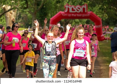 SOUTHAMPTON, UK - July 1 2018: Race for Life, women run and walk to raise money for Cancer Research charity, in Southampton UK. Women and children dressed up and walking under trees with heart sign.