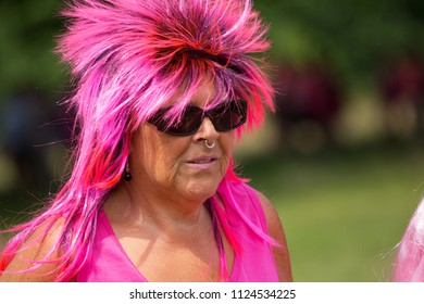 SOUTHAMPTON, UK - July 1 2018: Race for Life, women run and walk to raise money for Cancer Research charity, in Southampton UK. Woman With Pink Wig, a nose ring and sunglasses walking the race.
