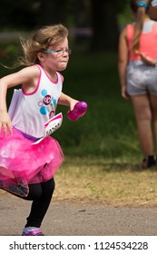 SOUTHAMPTON, UK - July 1 2018: Race for Life, women run and walk to raise money for Cancer Research charity, in Southampton UK. Girl dressed in a tutu and holding a water bottle running.