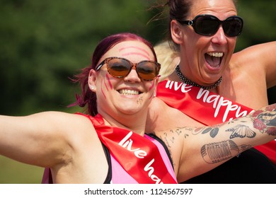 SOUTHAMPTON, UK - July 1 2018: Race for Life, women run and walk to raise money for Cancer Research charity, in Southampton UK. Women with Sashes saying Live happy.