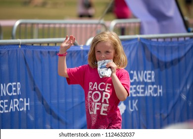 SOUTHAMPTON, UK - July 1 2018: Race for Life, women run and walk to raise money for Cancer Research charity, in Southampton UK. Girl with Race For Life tshirt, waving with Cancer Research UK Banner.