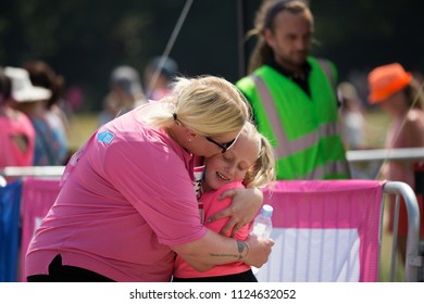 SOUTHAMPTON, UK - July 1 2018: Race for Life, women run and walk to raise money for Cancer Research charity, in Southampton UK. Mother and daughter hugging after finishing the Race for Life.