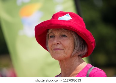 SOUTHAMPTON, UK - July 1 2018: Race for Life, women run and walk to raise money for Cancer Research charity, in Southampton UK. Older lady wearing a red hat looking sophisticated, having finished race