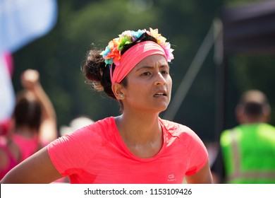 SOUTHAMPTON, UK - July 1 2018: Race for Life, women run and walk to raise money for Cancer Research charity, in Southampton UK. Woman dressed in pink wearing a hairband tired after running the race.