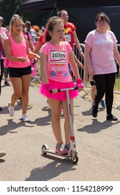 SOUTHAMPTON, UK - July 1 2018: Race for Life, women run and walk to raise money for Cancer Research charity, in Southampton UK. Child called Aimee dressed in a tutu doing the race on a scooter.