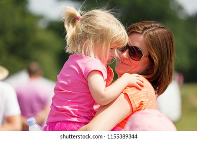 SOUTHAMPTON, UK - July 1 2018: Race for Life, women run and walk to raise money for Cancer Research charity, in Southampton UK. Mother and daughter smiling and hugging, showing each other love.