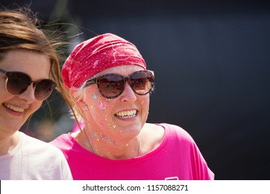 SOUTHAMPTON, UK - July 1 2018: Race for Life, women run and walk to raise money for Cancer Research charity, in Southampton UK. Two ladies laughing together, one with head scarf recovering from cancer
