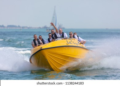 Southampton Water, Hampshire, UK; 7th July 2018; Yellow Powerboat, Jet Viper at High speed in Southampton Water Operated by Saber Powersports With Group of Male Passengers