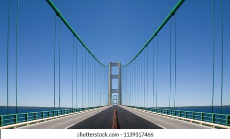 A south-bound view from the center of the highway that runs over the Mackinac Bridge. The first tower is in the center of the image with the second visible through an opening in the first.