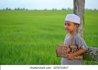 Southeast Asian boy reciting Al-Quran or Quranic during fasting month (Ramadan). Ramadan are sacred month among Muslim all over the world. On the book cover written with Al-Quran (Quranic Book)