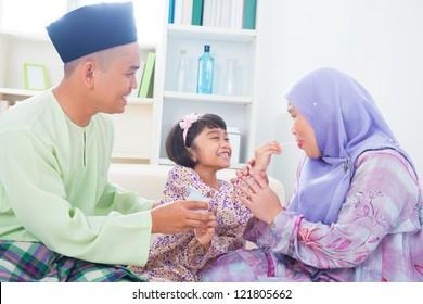 Southeast Asian child feeding mother yogurt. Malay Muslim family living lifestyle