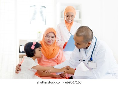 Southeast Asian child patient consulting medical doctor. Muslim family. Little girl with broken arm doing health check.