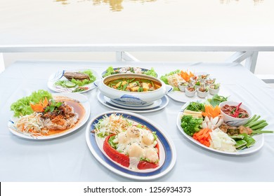 Southeast Asian cuisine set, Japanese shrimps with salad, Fish organs sour soup Thai style, Fish sauce Southern style, fried thread-fin fish Chinese style, served on white table-cloth with riverside.