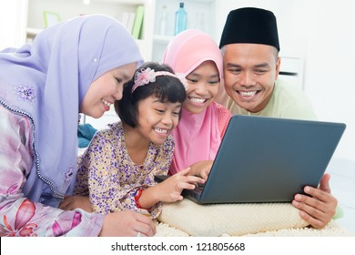 Southeast Asian family browsing internet at home. Lying on floor using computer laptop.