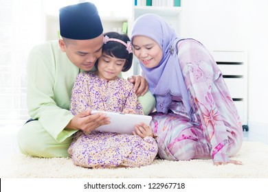 Southeast Asian family using computer internet at home. Muslim family living lifestyle