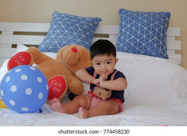 southeast Asian smiling kids sitting on white bed and toy. show hand up to pay respect in Thai culture.