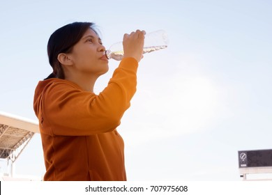 Southeast asian sport girl in orange Jacket drinking water from bottle at sport complex with beautiful sky