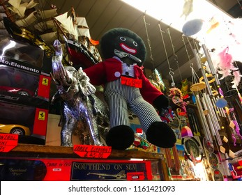 Southend On Sea, UK - 11 July 2018: Vintage old racist controversial golliwog mascot soft toy doll on a dusty shelf among many trinkets for sale inside a souvenir shop at the seaside.